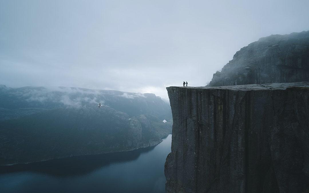Två människor syns långt borta på ett högt berg