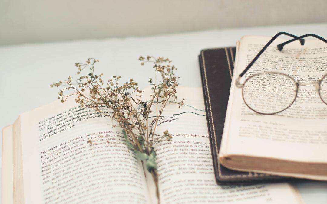 Ett par glasögon och en torkad blomma ligger ovanpå ett par böcker